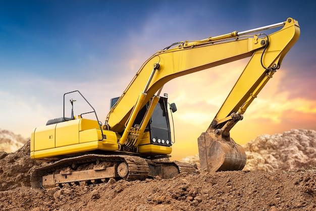 Excavatrice pelleteuse sur le sol sur un chantier de construction au coucher du soleil Photo Premium