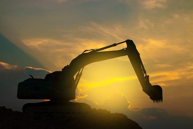 Les excavatrices travaillent dur sur le ciel coucher de soleil. Photo Premium