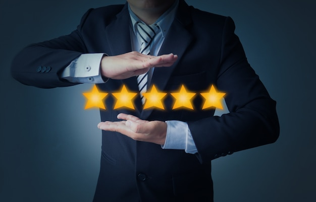Excellent service et meilleure expérience client ou bon client, homme d'affaires affichant une note de 5 étoiles sur fond bleu foncé Photo Premium