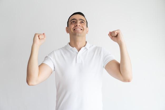 Excité beau jeune homme célébrant le succès et faire un geste oui. Photo gratuit