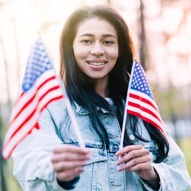 Excité femme ethnique avec des drapeaux américains de souvenir Photo gratuit
