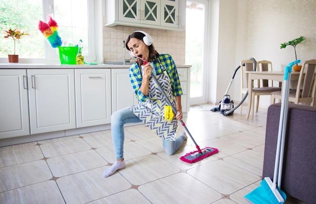 Excité Et Heureux Belle Jeune Femme Dans Un Tablier Nettoie Le Sol Dans Sa Cuisine à La Maison Et Danse Photo Premium