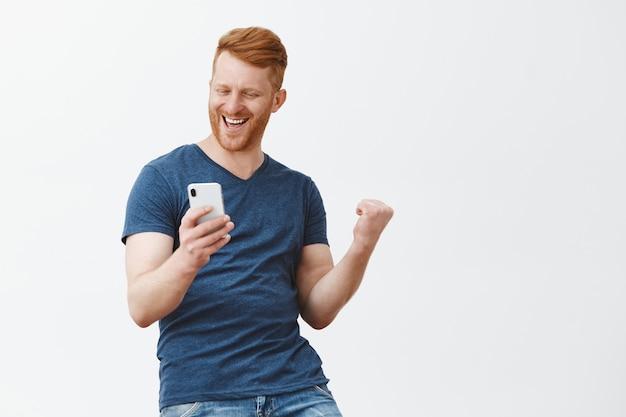 Excité Heureux Et Célébrant Bel Homme Rousse Avec Des Poils, Levant Le Poing Dans Le Geste De La Victoire, Tenant Le Smartphone Photo gratuit
