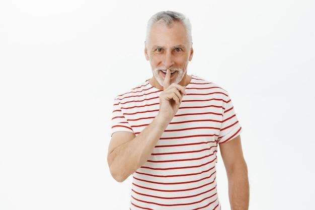 Excité Homme Barbu Senior Shushing Et Souriant Amusé Photo gratuit