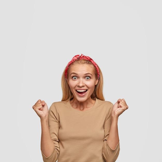 Excité Jeune Femme Blonde Posant Contre Le Mur Blanc Photo gratuit