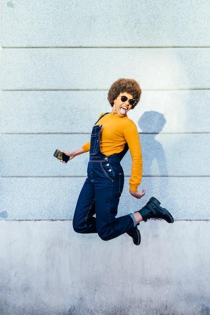 Excité De Jeune Femme Noire Sautant Avec Un Smartphone. Photo Premium