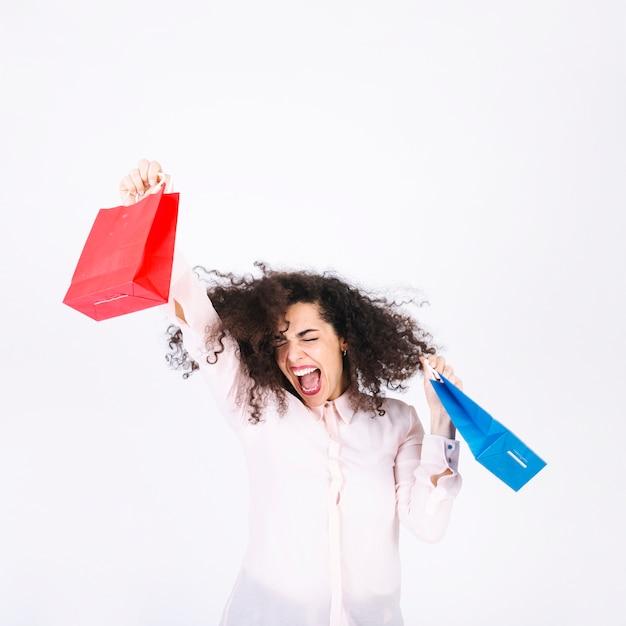 Excité de jeune femme avec des sacs en papier Photo gratuit
