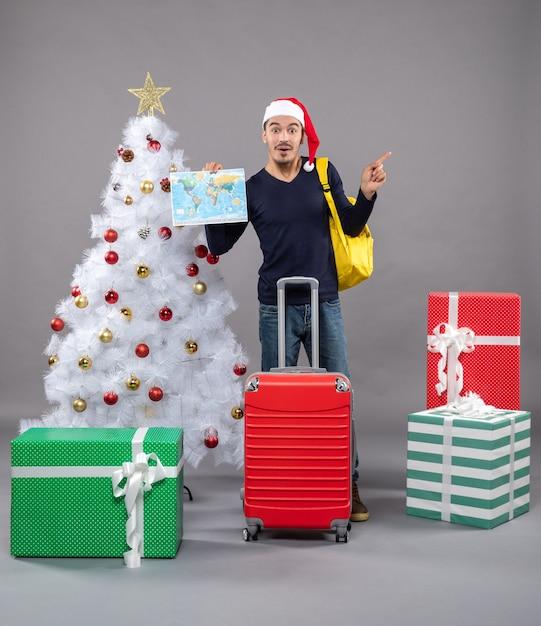 Excité Jeune Homme Avec Sac à Dos Jaune Tenant La Carte Près De L'arbre De Noël Blanc Sur Fond Gris Photo gratuit