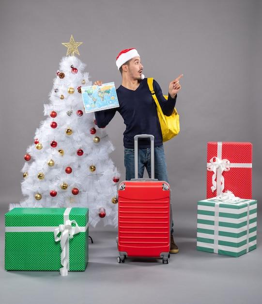 Excité Jeune Homme Avec Sac à Dos Jaune Tenant La Carte Près De L'arbre De Noël Sur Fond Gris Photo gratuit