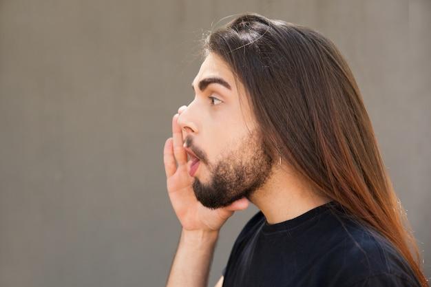 Excité mec aux cheveux longs annonçant des nouvelles importantes Photo gratuit