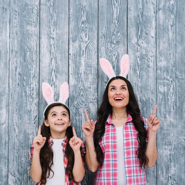 Excité mère et fille avec des oreilles de lapin pointant le doigt vers le haut sur un fond en bois Photo gratuit
