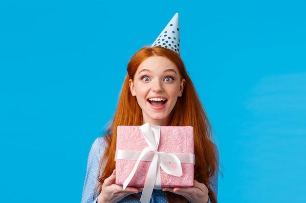 Excitée Belle Femme Rousse Glamour Aux Yeux Bleus Expression Heureuse, Recevez Un Joli Cadeau Rose, Présent Enveloppé Dans Une Boîte, Souriant Amusé, Fête Son Anniversaire En B-day Cap Photo Premium