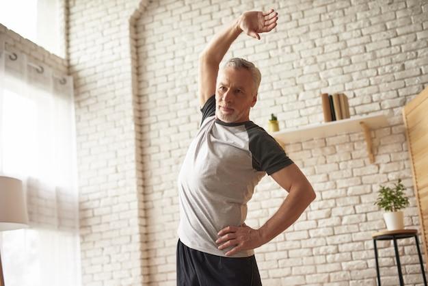 Exercices du matin dans la salle senior homme qui s'étend. Photo Premium