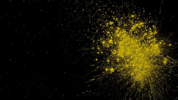 Explosion de couleur jaune sec sur fond noir Photo gratuit