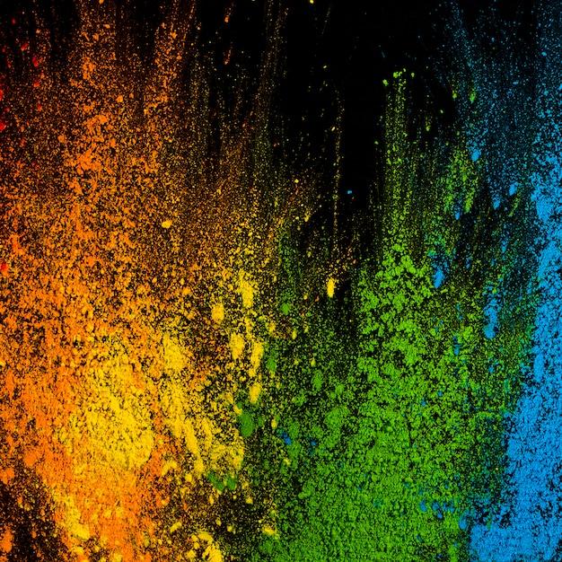 Explosion de couleurs holi sur la surface noire Photo gratuit
