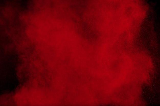 Explosion de poudre de couleur rouge sur fond noir Photo Premium