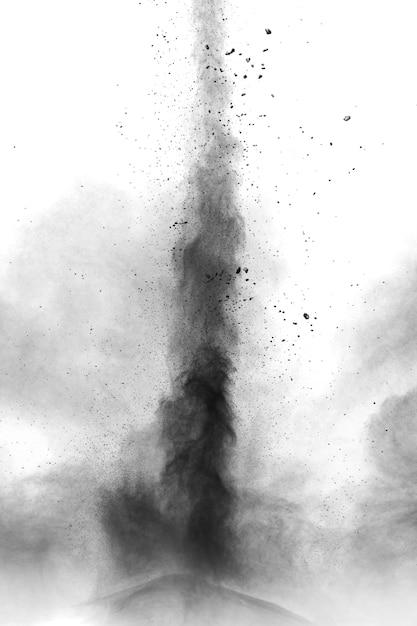 Explosion de poudre noire sur fond blanc. des particules de poussière noire éclaboussent. Photo Premium