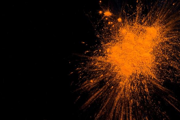 Explosion de poudre orange sur fond noir Photo gratuit