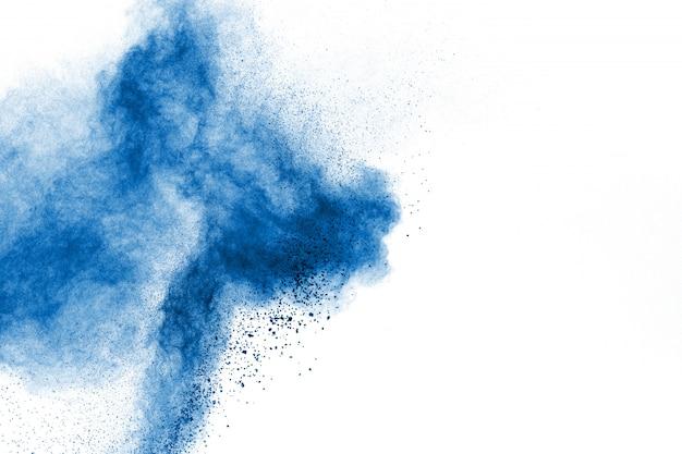 Explosion de poussière bleue abstraite sur fond blanc. figer le mouvement des particules bleues éclaboussant. Photo Premium