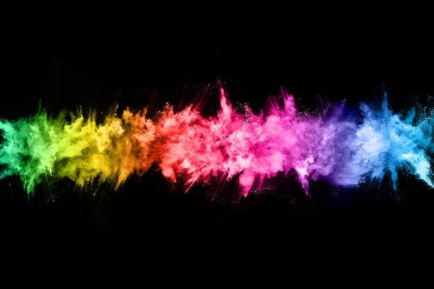 Explosion de poussières colorée abstraite sur fond noir. Photo Premium