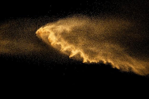 Explosion de sable de rivière à sec. éclaboussure de sable de couleur marron sur fond noir. Photo Premium