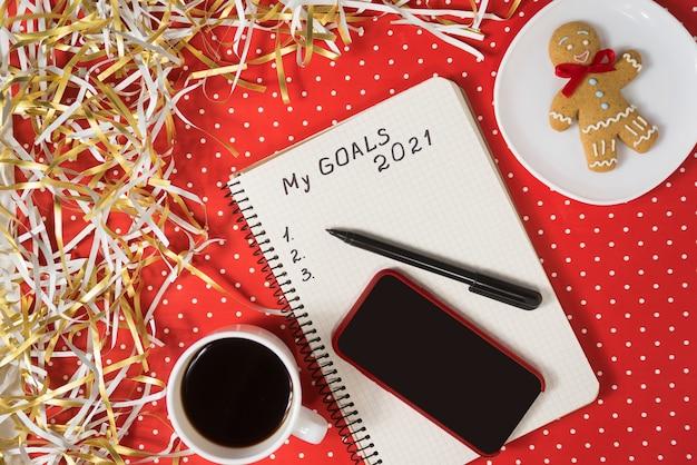 Expression De Mes Objectifs 2021 Dans Un Cahier, Un Stylo Noir Et Un Téléphone Intelligent. Pain D'épice Et Café Sur Fond Rouge. Photo Premium