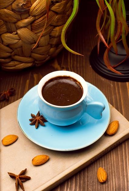 Expresso frais et savoureux. tasse bleue de café chaud aux amandes et anis Photo gratuit