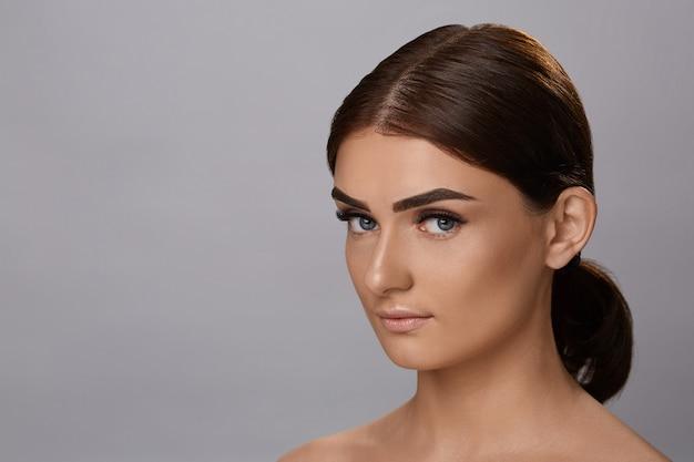 Extensions de cils. faux cils. gros plan de la belle jeune mannequin avec une peau douce et lisse et un maquillage facial professionnel. portrait d'une fille sexy avec de longs cils faux et un maquillage parfait. Photo Premium