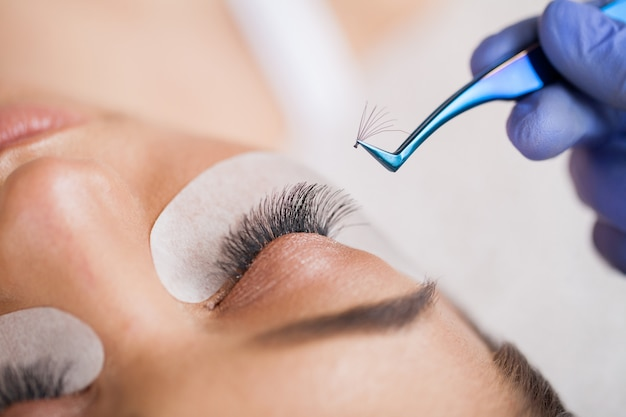Extensions De Cils. Faux Cils. Procédure D'extension De Cils. Styliste Professionnel Allongeant Les Cils Féminins. Maître Et Client Dans Un Salon De Beauté Photo Premium
