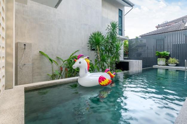 Extérieur maison avec piscine et licorne flottante dans la maison Photo Premium