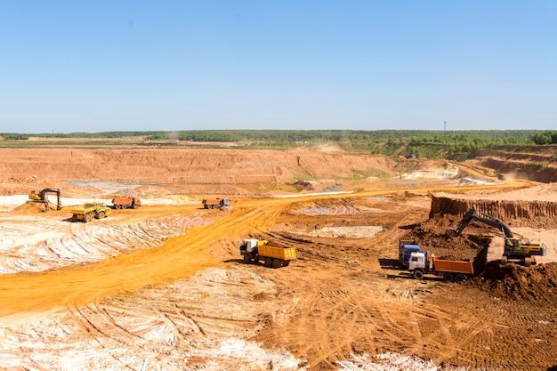 Extraction de sable dans la carrière. une pelleteuse charge du sable dans des camions à benne. Photo Premium
