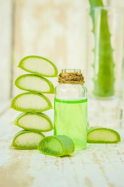 Extrait d'aloe vera dans une petite bouteille et des morceaux sur la table. mise au point sélective. Photo Premium