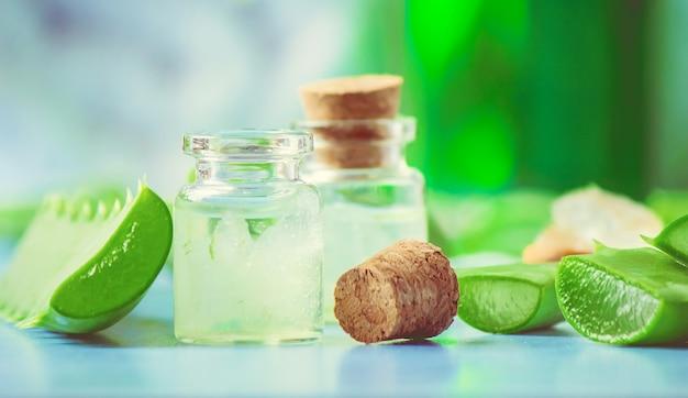 Extrait d'aloe vera dans une petite bouteille et morceaux sur la table. mise au point sélective. Photo Premium