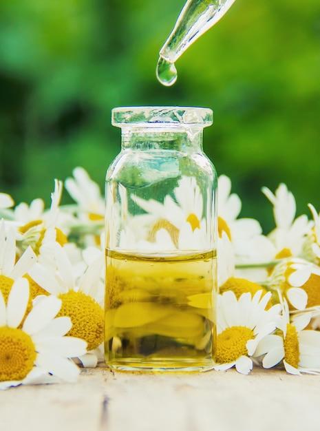 Extrait de camomille dans une petite bouteille. nature de la mise au point sélective. Photo Premium