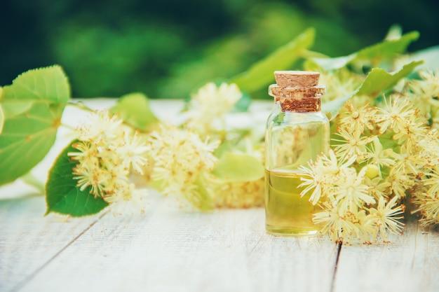 Extrait de tilleul et fleurs dans une petite bouteille. mise au point sélective. Photo Premium