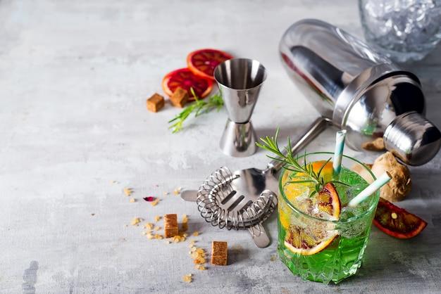 Fabrication de cocktail mojito. menthe, citron vert, verre, glace, ingrédients et shaker Photo Premium