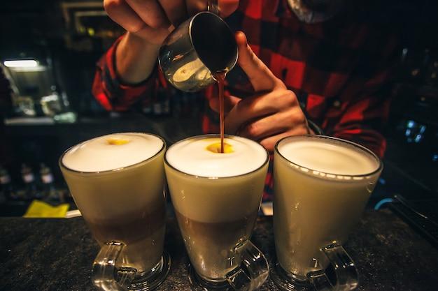 Fabrication du café. barista verse la cannelle dans de nouvelles tasses de café au lait ou de cappuccino. Photo Premium