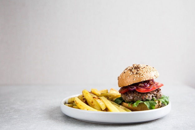 Fabriquer un burger de bœuf fait maison et des frites. fond clair, espace copie. Photo Premium