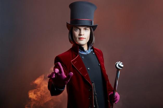 Fabuleux homme de cirque avec un chapeau et un costume rouge posant dans la fumée Photo Premium