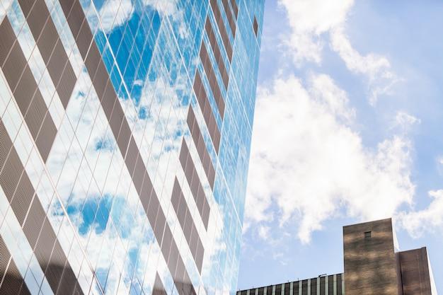 Façade abstraite d'un gratte-ciel moderne avec des nuages réfléchis Photo Premium