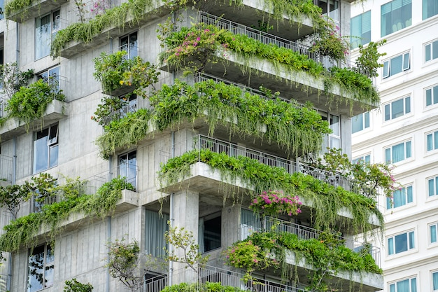 Façade De Bâtiments écologiques Avec Des Plantes Vertes Et Des Fleurs Sur Le Mur De Pierre De La Façade De La Maison Dans La Rue De Danang, Vietnam Photo Premium