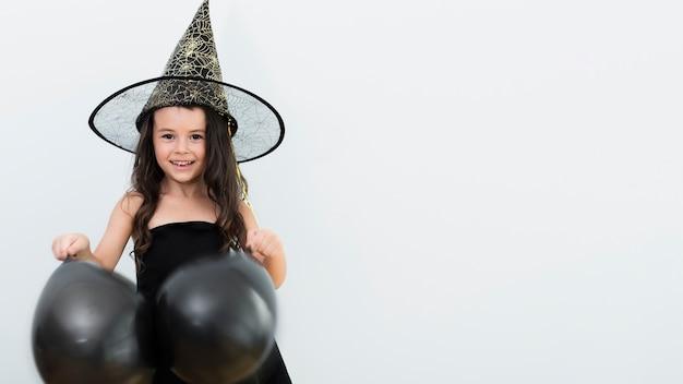 Façade vue de petite fille en costume de sorcière pour halloween Photo gratuit