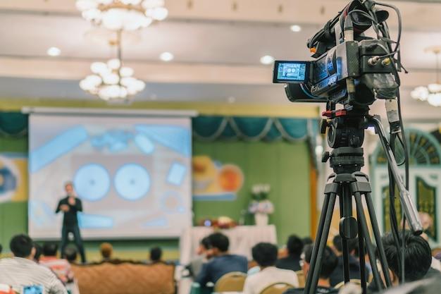 Face arrière du caméraman vidéo prenant une photo au haut-parleur asiatique Photo Premium