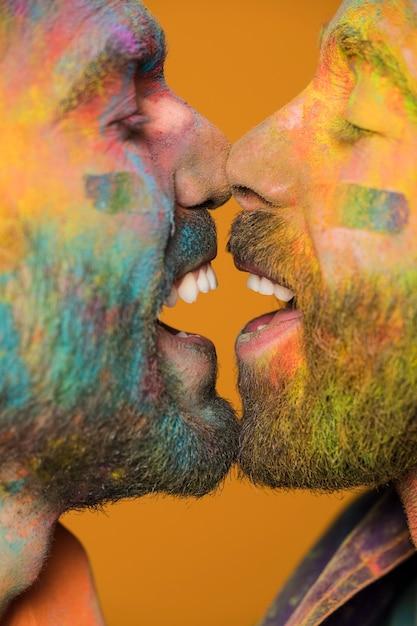 Face à face des hommes homosexuels heureux dans la peinture arc en ciel Photo gratuit