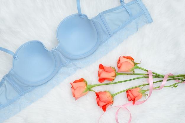 Face interne du corsage bleu avec dentelle sur fourrure blanche et roses orange. Photo Premium