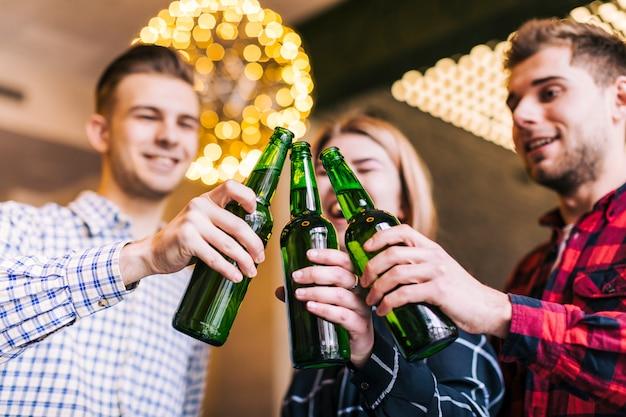 Faible angle de vue des amis heureux tinter des bouteilles de bière Photo gratuit