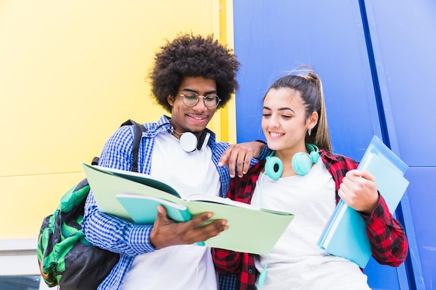 Faible angle de vue d'un couple d'adolescents lisant le livre debout contre un mur coloré Photo gratuit