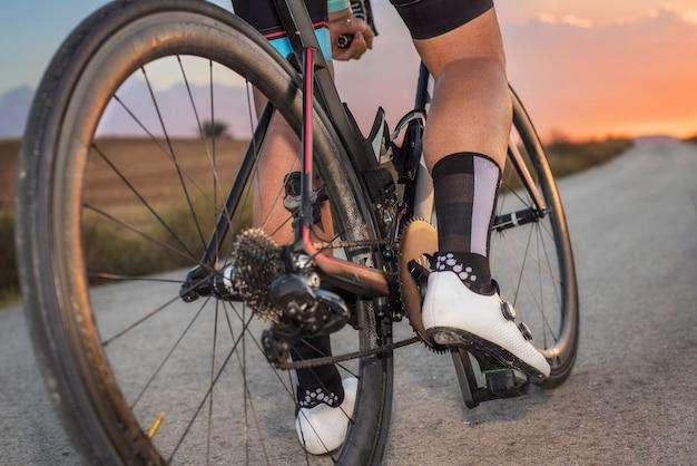 Faible angle de vue du cycliste debout avec vélo au coucher du soleil Photo Premium