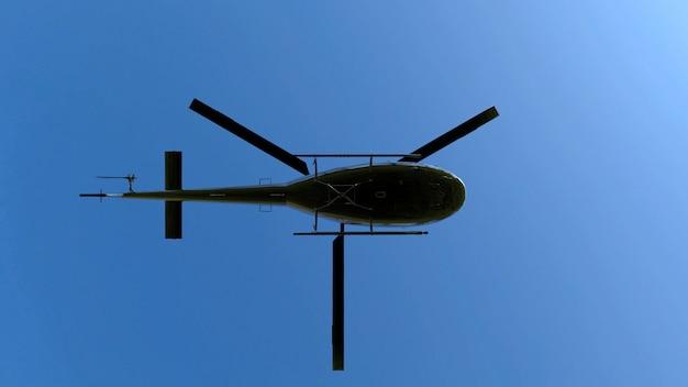 Faible angle de vue d'hélicoptère en métal noir volant sur ciel bleu. Photo Premium
