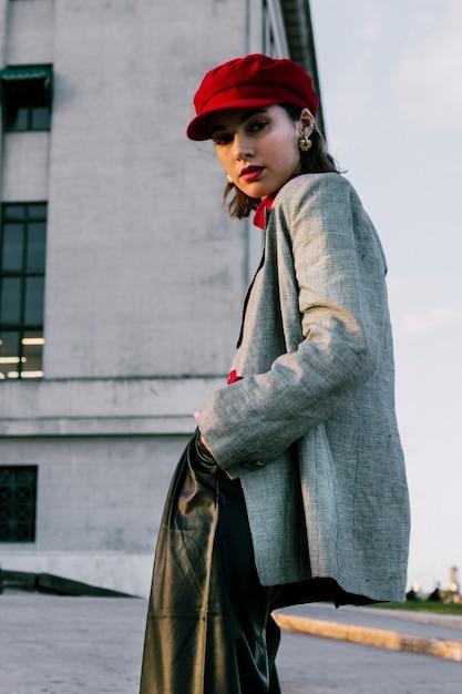 Faible angle de vue de la jeune femme à la mode avec ses mains dans la poche Photo gratuit